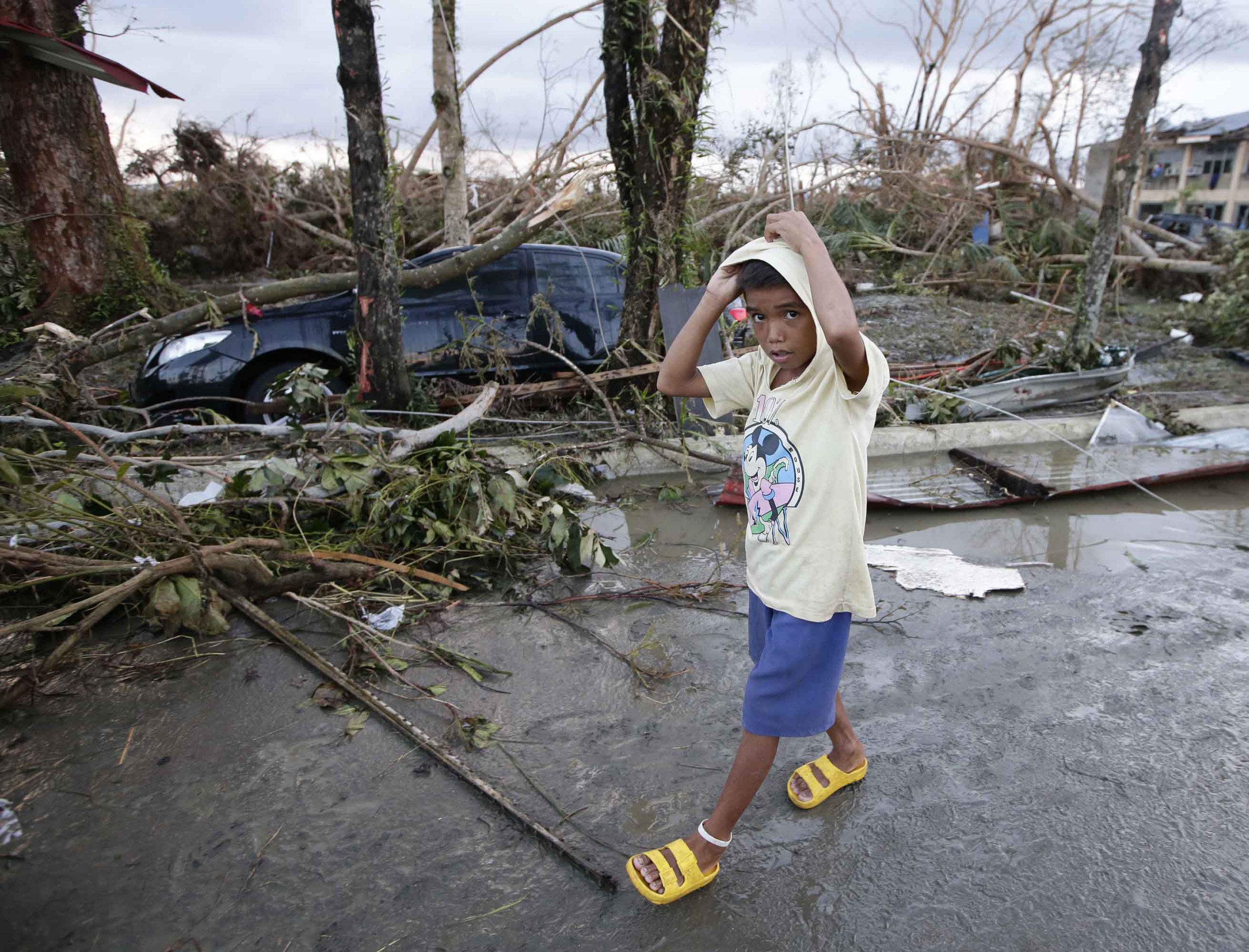 © AP Photo/Bullit Marquez. A boy in Tacloban, in the central Philippines, walks past the devastation brought by Typhoon Haiyan.