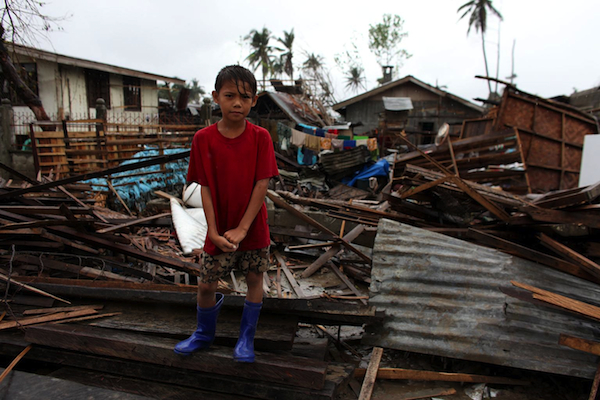 A 9-year-old boy stands amid homes destroyed by Typhoon Bopha in southeastern Mindanao last December. A recent earthquake in Bohol has further worsened the humanitarian situation in the Philippines. © UNICEF/NYHQ2012-1720/JOSH ESTEY