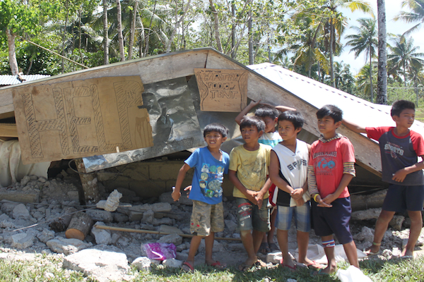 Children affected by the earthquake stand in front of a collapsed house in Bohol, Philippines. ©UNOCHA 2013/JAddawe