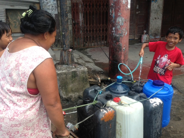 Kent Page, 2013. A family collects water at one of the 30,000 water access points across Tacloban that UNICEF and its partners restored this weekend.
