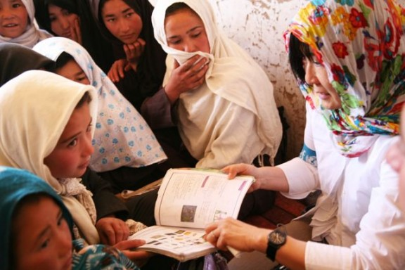 Susan Findel and a group of students read together. © Alistair Gretarsson, UNICEF.