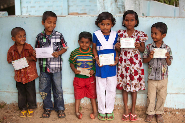 Bangladeshi children stand with their birth registration cards.
