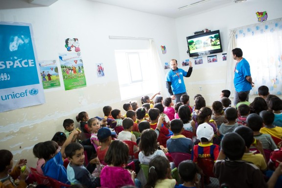 UNICEF support workers talk to children in a Child-Friendly Space in Domiz camp for Syrian refugees in Iraq. © UNICEF/UKLA2013-00799/Karin Schermbrucker