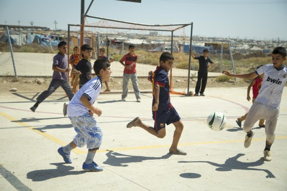Syrian refugee children start a game of soccer at the Domiz camp in Iraq. © UNICEF/UKLA2013-02433/Sharron Lovell
