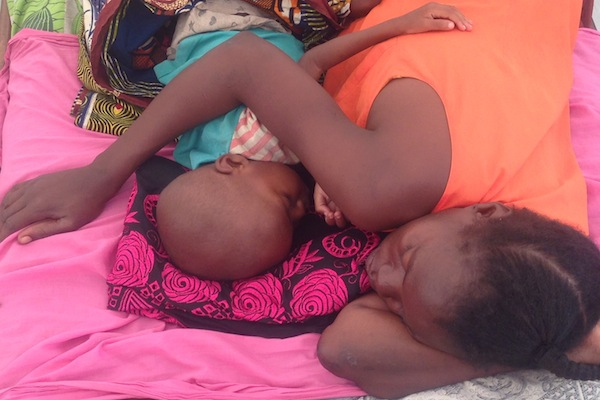 A mother and her child sleep arm-in-arm at the only pediatric hospital in the Central African Republic. All children are treated free of charge at the UNICEF-supported hospital.