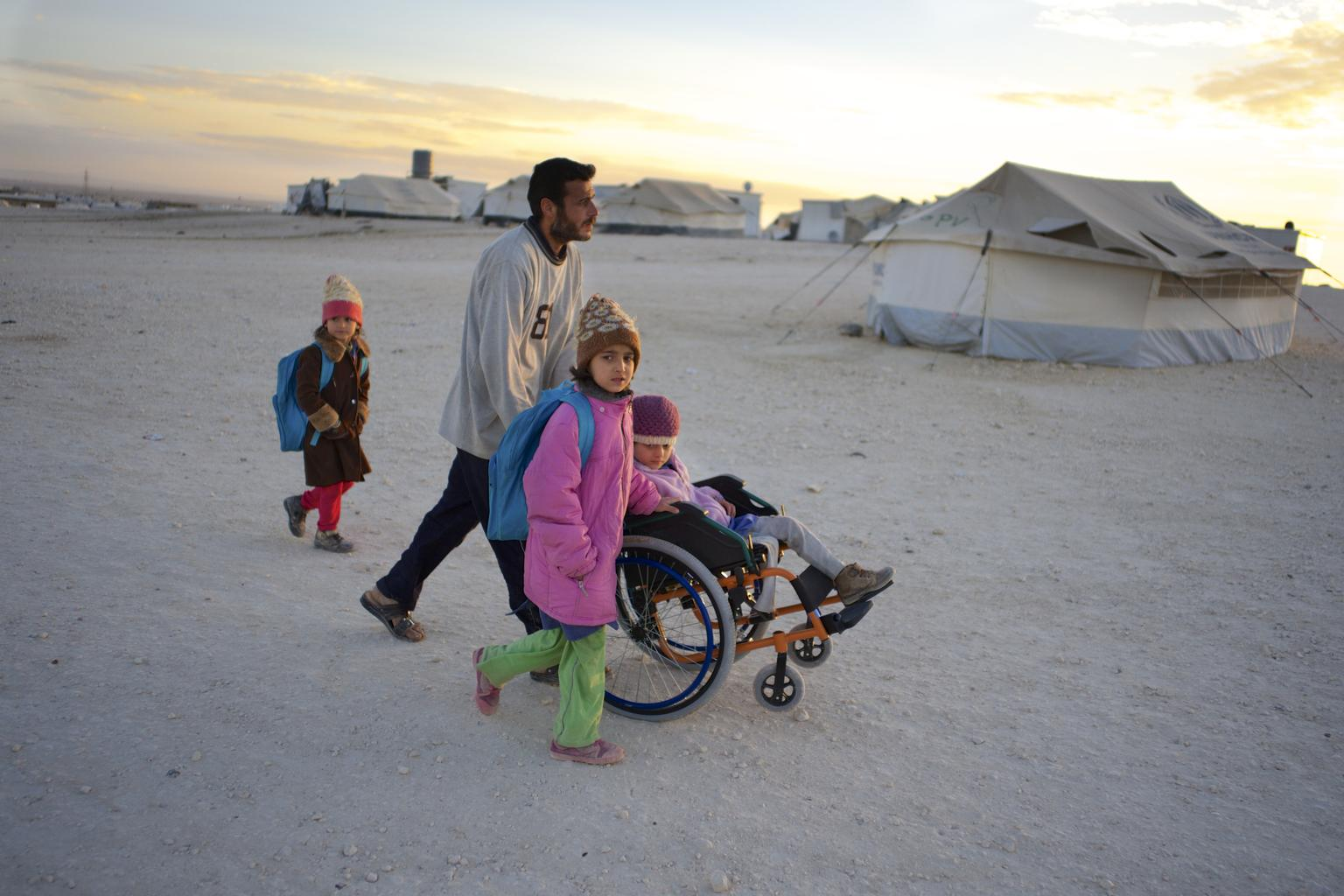 On 26 November 2013 in Jordan, a man pushes his daughter  in a wheelchair, in a refugee camp near the Syrian border