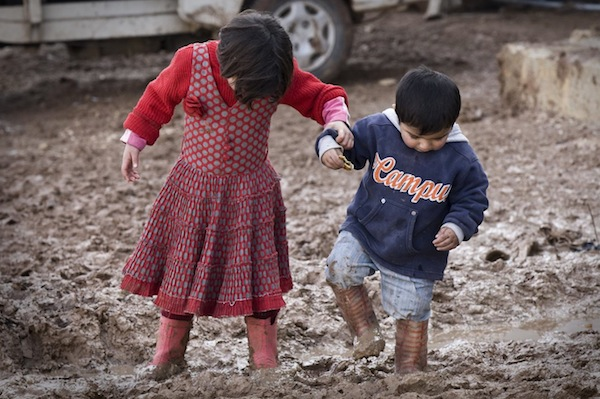 A Syrian girl and boy walk across the muddy grounds of the Bab Al Salame displacement camp in Aleppo Governorate.