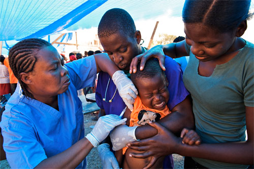 A boy accompanied by his mother cries while being vaccinated, at Sylvio Cator Stadium in the center of Port-au-Prince.
