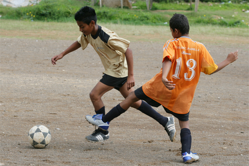 Children playing soccer at