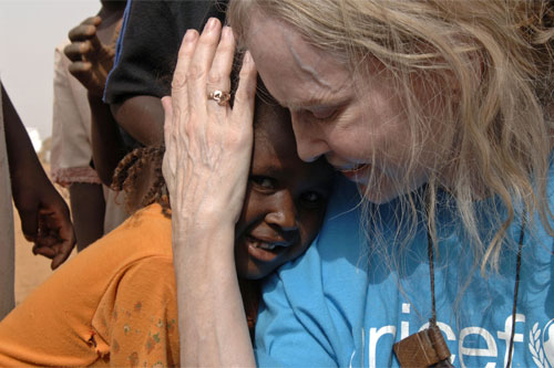 UNICEF Goodwill Ambassador Mia Farrow  is greeted by children at the Dereige camp for people displaced by the conflict, near Nyala, capital of South Darfur State in June 2006.