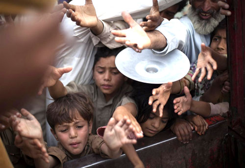 Displaced children crowd an ice truck during a distribution in the Swabi Camp in North-West Frontier Province (NWFP). Nearly 5,000 people are living in the UNICEF-supported camp.