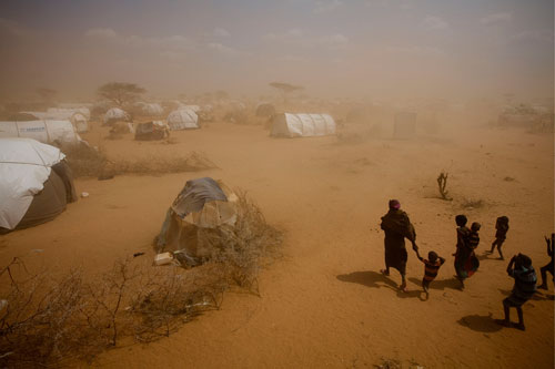 A woman and several children walk to their tent, in an area for new arrivals in the Dagahaley refugee camp in North Eastern Province, near the Kenya-Somalia border. The camp is among three that comprise the Dadaab camps.