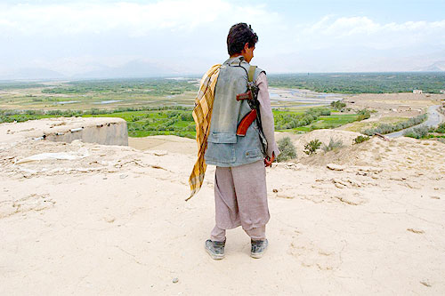 Afghanistan - Mohammad Amin, 18, a former child soldier, looks at the countryside from atop the crumbling roof of a barracks in the village of Bagram on the Shomali Plain in the Central Region province of Parwan.