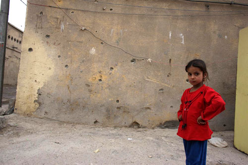 A girl stands near a bullet-riddled wall in the Sadr City neighborhood of Baghdad.