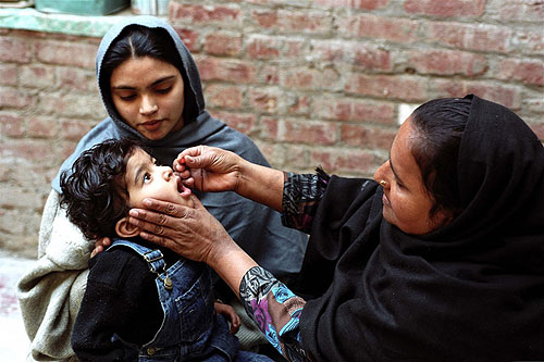 A Lady Health Worker (LHW) giving Vitamin A to a young girl child in her Health House. Sialkot City. Punjab Province, Pakistan.