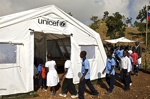 Children file into a UNICEF tent school, on the first day of classes in the remote village of Jacquot Merlin, above Port-au-Prince, the capital. UNICEF is also providing the children with educational supplies via a newly delivered school-in-a box kit, containing teaching and learning materials for 80 students.