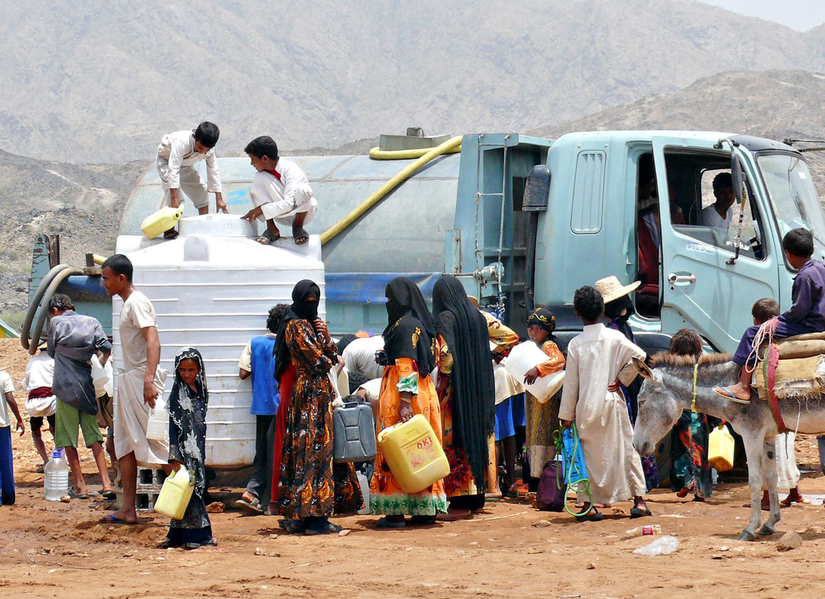 People collect water from one of 20 UNICEF-supplied water tanks in a displacement camp,in Yemen in 2009.